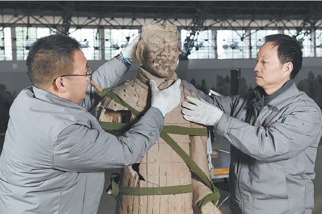 Лань Дэшэн (справа) и его коллега Ван Дунфэн реставрируют терракотового воина.