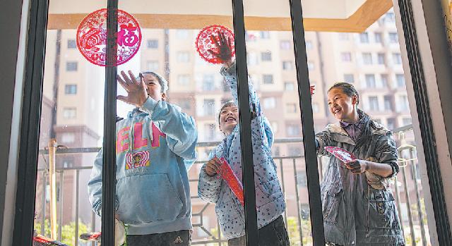 Семья расклеивает наклейки, посвященные Празднику весны, в своем новом доме в городе Цюйцзин, провинция Юньнань, 11 февраля. Они стали одними из многих людей, преодолевших черту бедности.