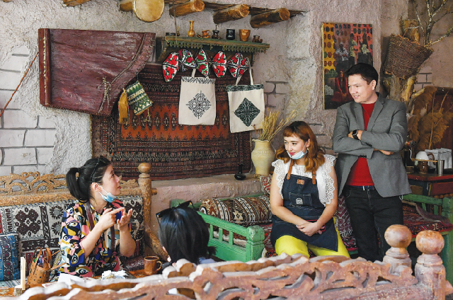 Мардан Аблимит (справа) и его жена Дильнар Акбар беседуют с посетительницей в своей кофейне Kashgar Corner.