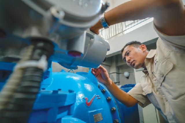 Инженер по техническому обслуживанию проверяет водоочистное оборудование на водонапорной станции в Цзяши.