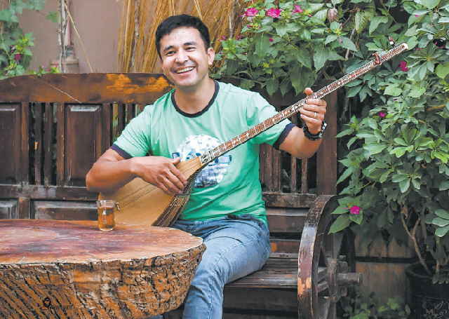 Мужчина играет на дутаре в Старом городе.
