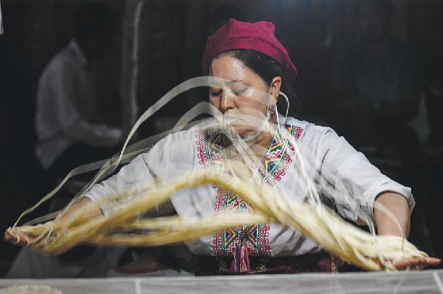 Шеф-повар готовит лапшу перед прилавком на ночном рынке в Кашгаре, август 2019 года.