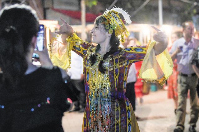 Девушка в народном костюме танцует на ночном рынке в Кашгаре, 12 августа 2019 года.