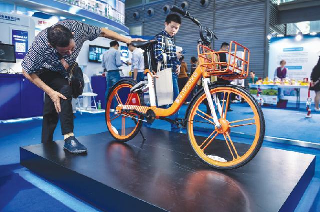 Посетители изучают велосипед, оснащенный чипом позиционирования Beidou, в ходе промышленной выставки в г. Шэньчжэнь, провинция Гуандун.